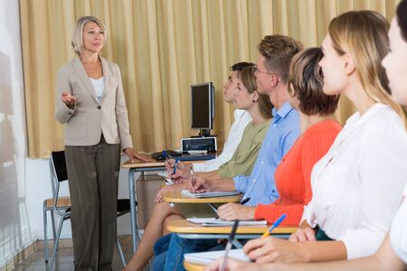 Group of students attentively listening to lecture of female teacher in classroom Standard-Bild