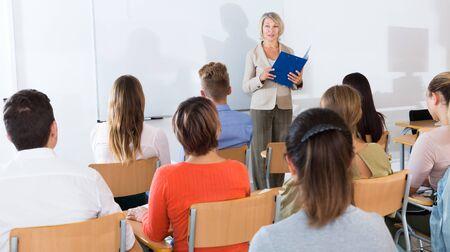 Elegant female teacher lecturing to students in auditorium