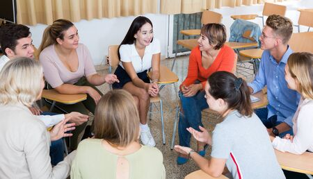 Cheerful student group lively discussing while sitting in circle in auditorium
