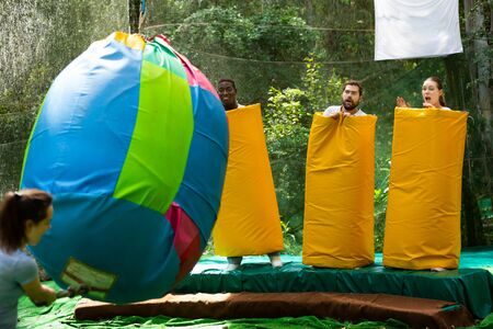 Jolly adults dressed in large inflatable pasta pretending to be afraid of being hit by young woman with big bag in amusement park