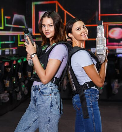 Two positive cheerful  girls standing back and holding guns during laser tag game in dark labyrinth