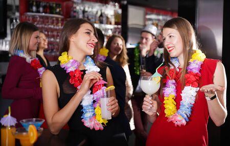 Cheerful girls dancing and toasting drinks on Hawaiian party in bar Фото со стока