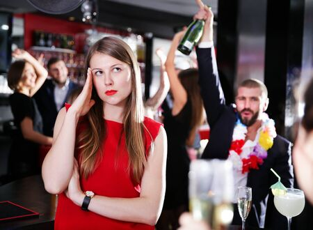 Offended young woman on background with drunk man on party at nightclub