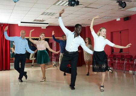 Couples of young people practicing twist movements together at modern dance studio