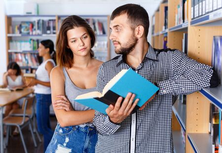 Young diligent people spending time together, choosing and discussing books in public library Stock fotó