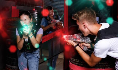 Group of smiling friends holding colored laser guns during laser tag game in labyrinth