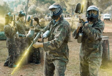 Two vigorous paintball players in full gear having fun before game outdoors