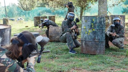 circumspect teams facing on battlefield in outdoor paintball arena during the match