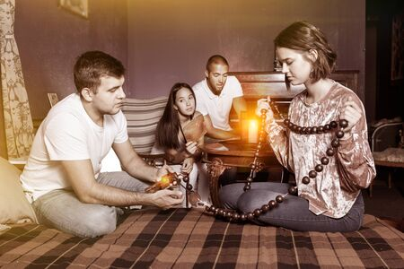 Group of young adults inspecting wooden rosary, trying to find solution of conundrum in escape room with antique furnitures Stock Photo