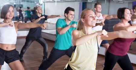 Young happy people dancing elements in dancing hall indoor