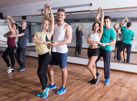 Group of active adults dancing salsa together in dance studio and smiling 版權商用圖片