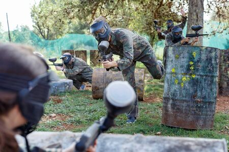 Team of happy cheerful positive smiling  people playing paintball on battlefield outdoor, running with guns Фото со стока