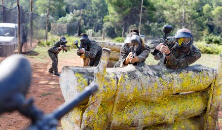 Portrait of team of  positive smiling adult people playing on paintball battlefield outdoor