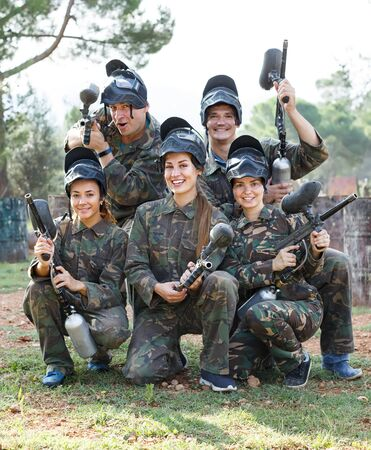 Portrait of joyous team of paintball players with marker guns ready for game outdoors