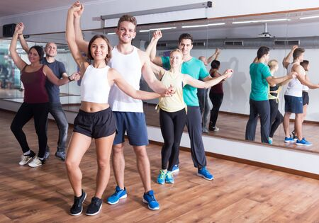 Group of smiling people dancing salsa together in dance studio