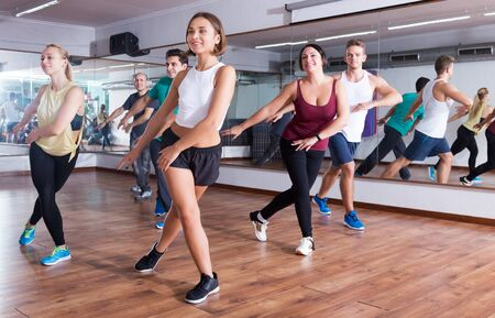 Happy active adult men and ladies dancing lesson