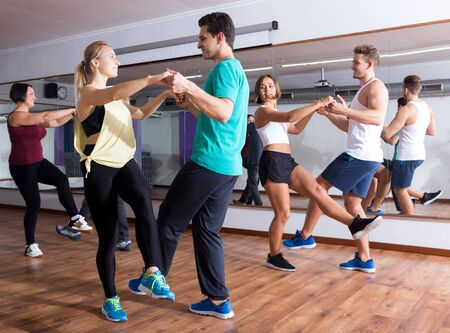 Young cheerful men and women dancing swing in dance hall