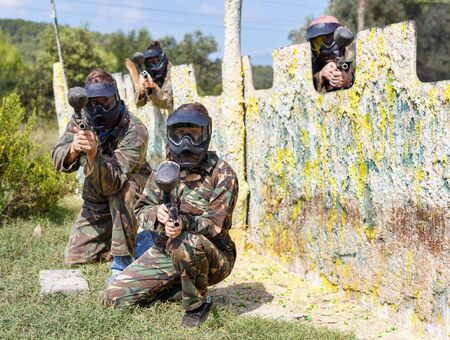 Portrait of team of positive  adult people playing on paintball battlefield outdoor