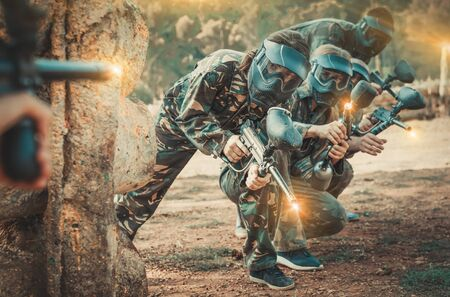 Paintball players of one team in camouflages and masks aiming with gun in shootout on battlefield