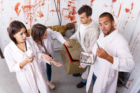 Young people trying to find solution of conundrum in closed space of lost room with bloody walls and zombi on table