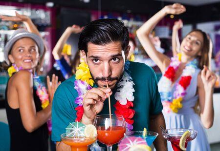 Dorosły mężczyzna pije koktajl alkoholowy na hawajskiej imprezie