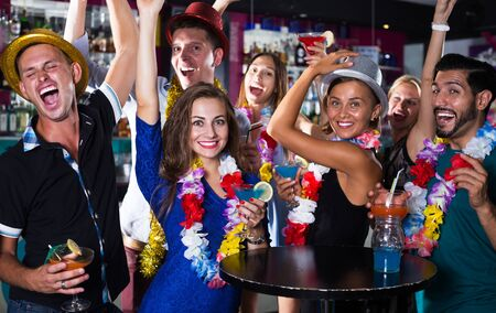 Amigos alegres bailan en la fiesta hawaiana en el bar