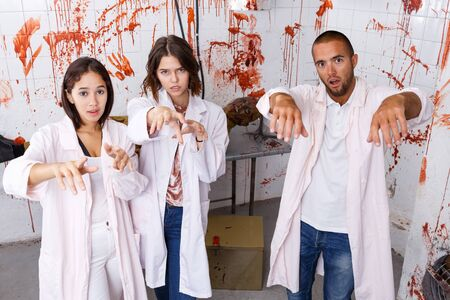 Young people having fun in closed space of lost room with bloody walls posing as zombies Stok Fotoğraf - 131334915