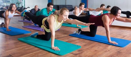 Positive young people relaxing and enjoying yoga elements