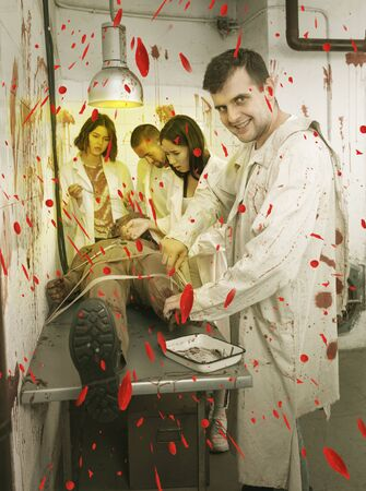 Guy with mad look standing over zombie mannequin with friends in quest room styled as abandoned surgical room with blood traces 스톡 콘텐츠