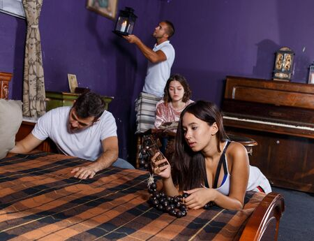 Group of young adults inspecting wooden rosary, trying to find solution of conundrum in escape room with antique furnitures Фото со стока