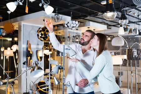 family couple choosing  suspension lamp in furniture showroom