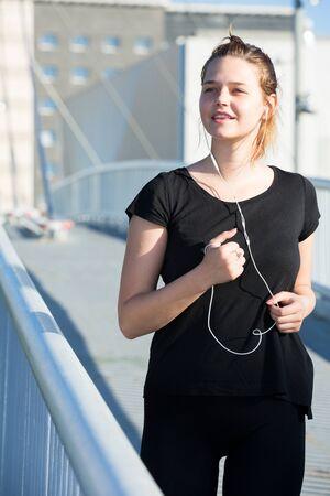 Young girl in black listening to music enjoying morning run on city bridge Stock Photo