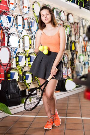Young women standing in skirt in sneakers in sporting goods store with racket and balls for tennis