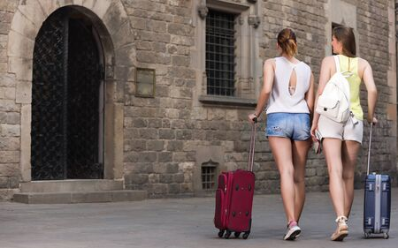 cheeful young greek tourist women friends walk in  town with suitcase