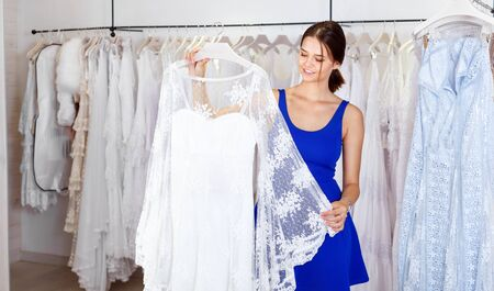 Ð¡heerful positive smiling girl choosing white gown in modern wedding shop