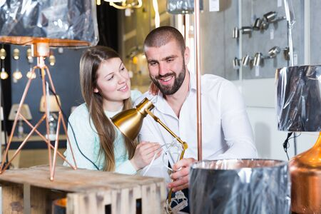 Portrait of family couple choosing lamp in furniture showroom 写真素材
