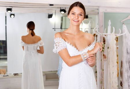 Young cheerful  smiling woman fitting luxury wedding dress at modern wedding salon 写真素材