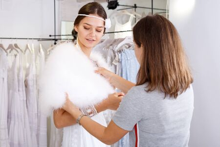 Young happy girl fitting wedding dress with help of shop assistant at modern wedding salon 写真素材