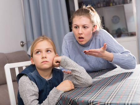 Serious adult mother scolding her teenage daughter at home