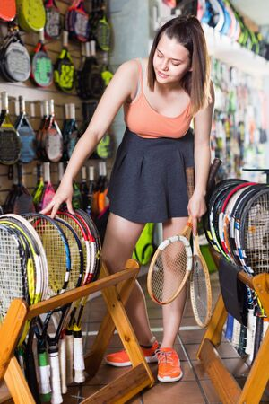 Young smiling girl standing in t-shirt in sporting goods store with racket