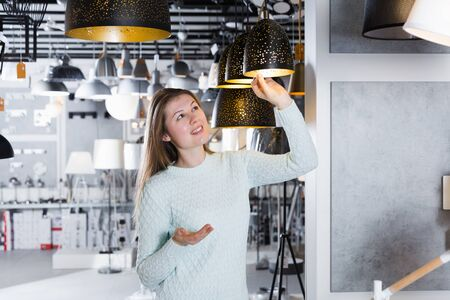 Young woman looking pendent lamp in  furniture  showroom 写真素材