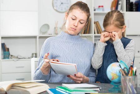 Mom scolds little daughter for poor grades in school Banque d'images