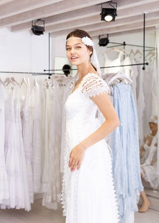 Young smiling woman flaunting dressed in wedding gown in wedding salon