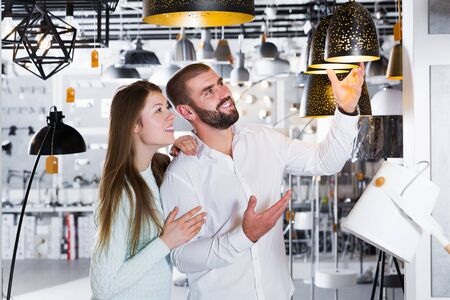 Portrait of smiling family couple choosing  suspension lamp in furniture showroom