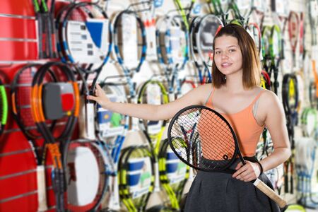 Happy brunette young woman holding in hand racket for badminton in sport shop