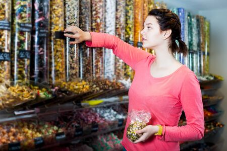 Glad woman posing to photographer picking different candies with  scoop in  cellophane bag 스톡 콘텐츠