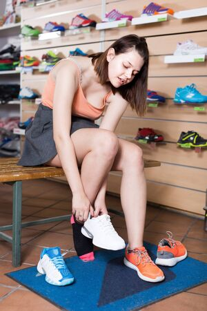 Smiling young girl buying professional sneakers in sport shop