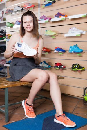 Positive young sportswoman trying professional shoes in sport store
