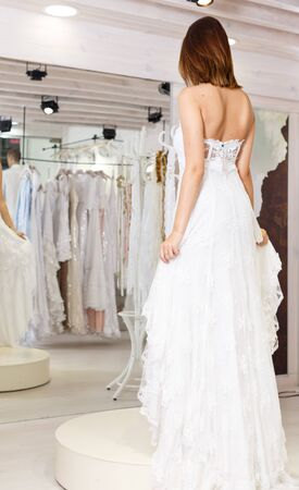Young happy girl fitting wedding dress at modern wedding salon