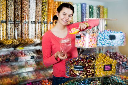 Pretty young woman posing to photographer picking different candies with  scoop in  cellophane bag